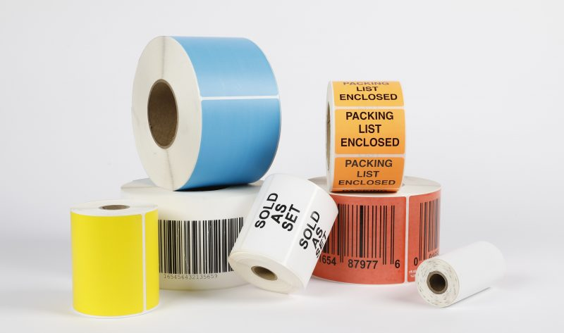 Colorful and white thermal labels are blank or have barcodes printed on them