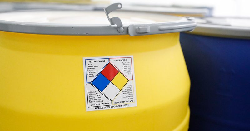 A drum with a color warning label sits in a factory