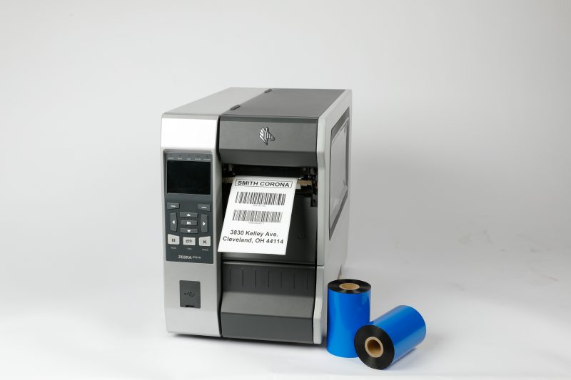 An industrial Zebra printer with a label.