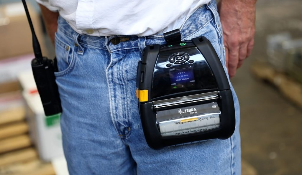 A Zebra ZQ630 mobile printer attached to a worker's belt loop.