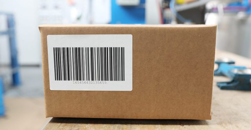 A barcode label printed using a flat head thermal printer is placed on a cardboard box