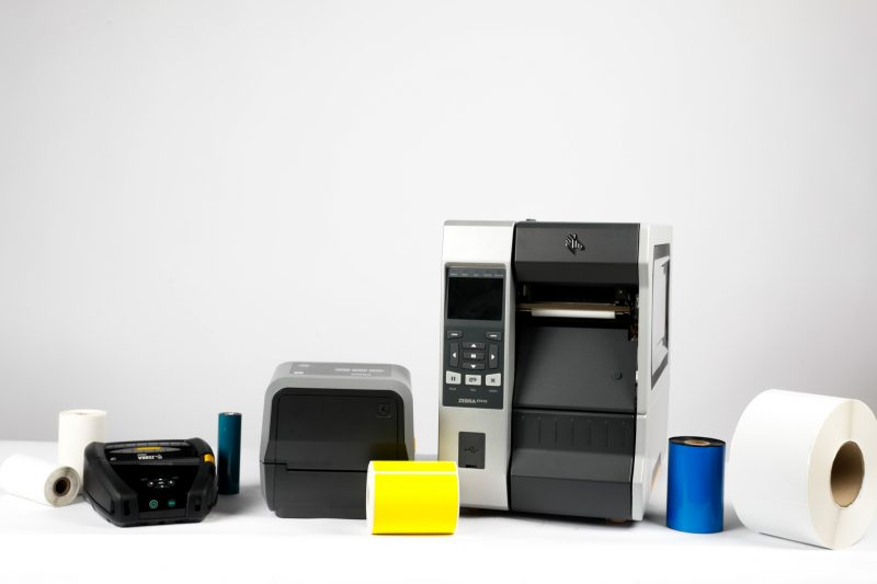 An industrial, desktop, and mobile printer sit with thermal labels and ribbons