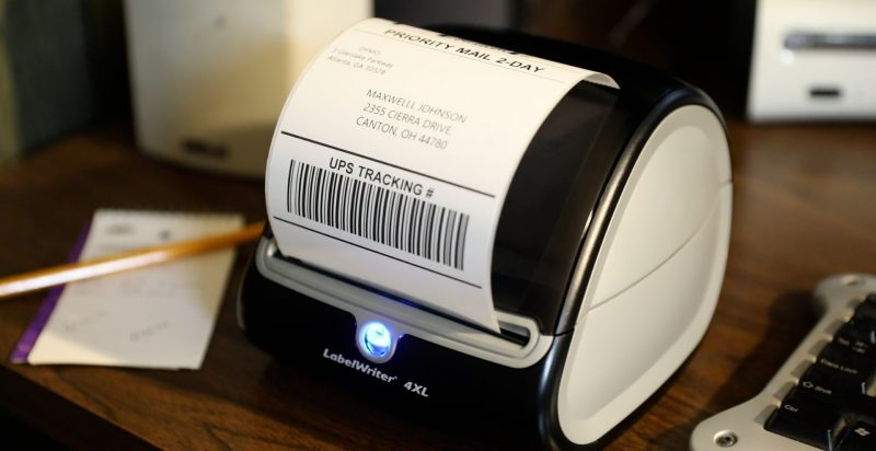 A DYMO 4LX printer with a shipping label printed