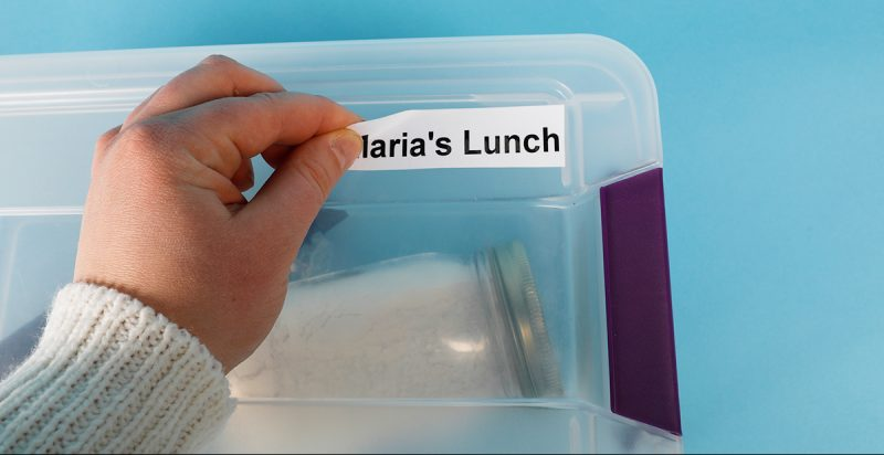 A label with removable adhesive is applied to a container