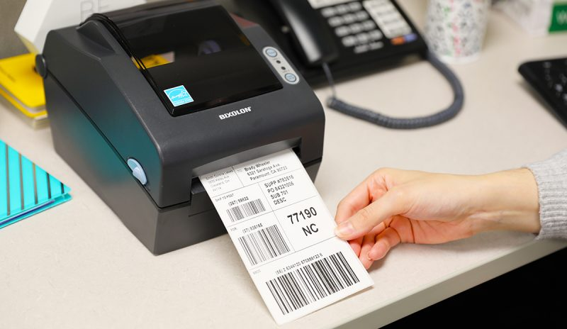 A Bixolon SLP-DX420 direct thermal label printer sits on a desk with a shipping label ready to go