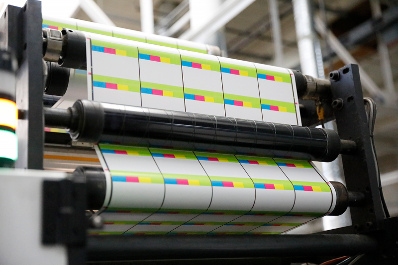 White and colored laminate are run through a die-cutting machine, making various label shapes and sizes.