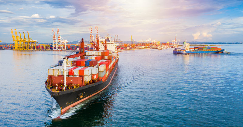 A container ship along a port transports supplies and goods.