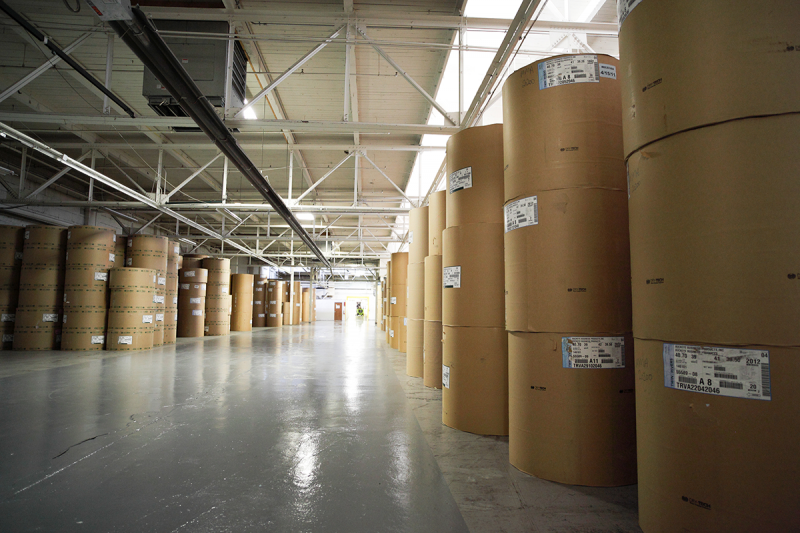 Raw materials for labels sit in a warehouse waiting to be moved.
