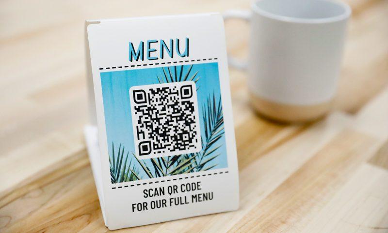 A dynamic QR code on a tabletop tent allows users to scan it with their phone to view the menu