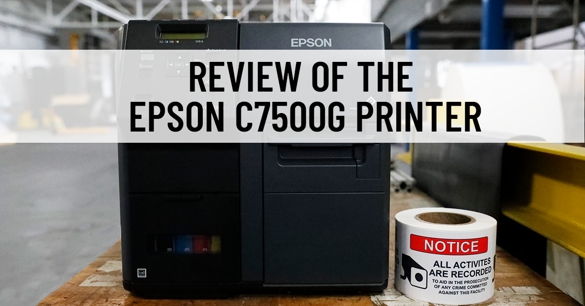 An Epson C7500G inkjet printer in a warehouse setting with a roll of GHS printed labels next to it
