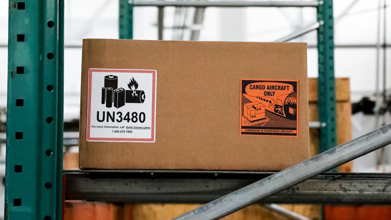A box with a UN 3480 lithium ion battery label and CAO battery label sits on a shelf in a warehouse