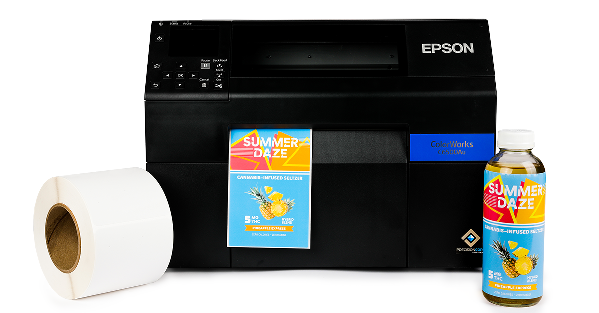 An Epson C6500Au inkjet printer with a color label printed, a roll of inkjet labels, and a product with a label applied