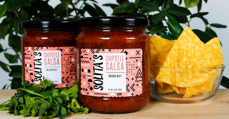 A prime label with vibrant colors is applied to a jar of salsa