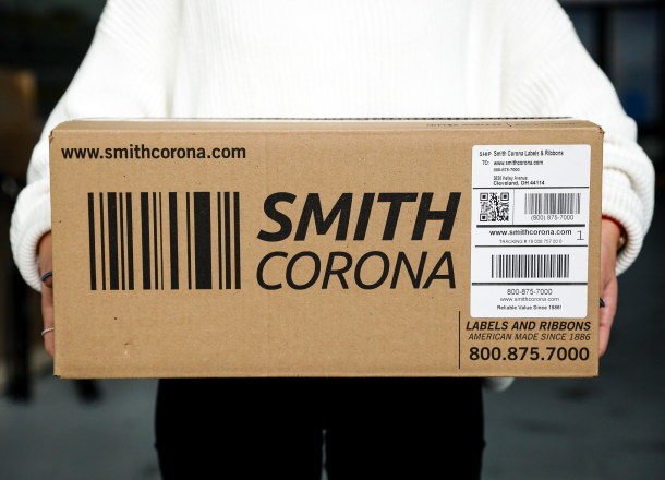 A Smith Corona package held by a person wearing a white shirt and black pants